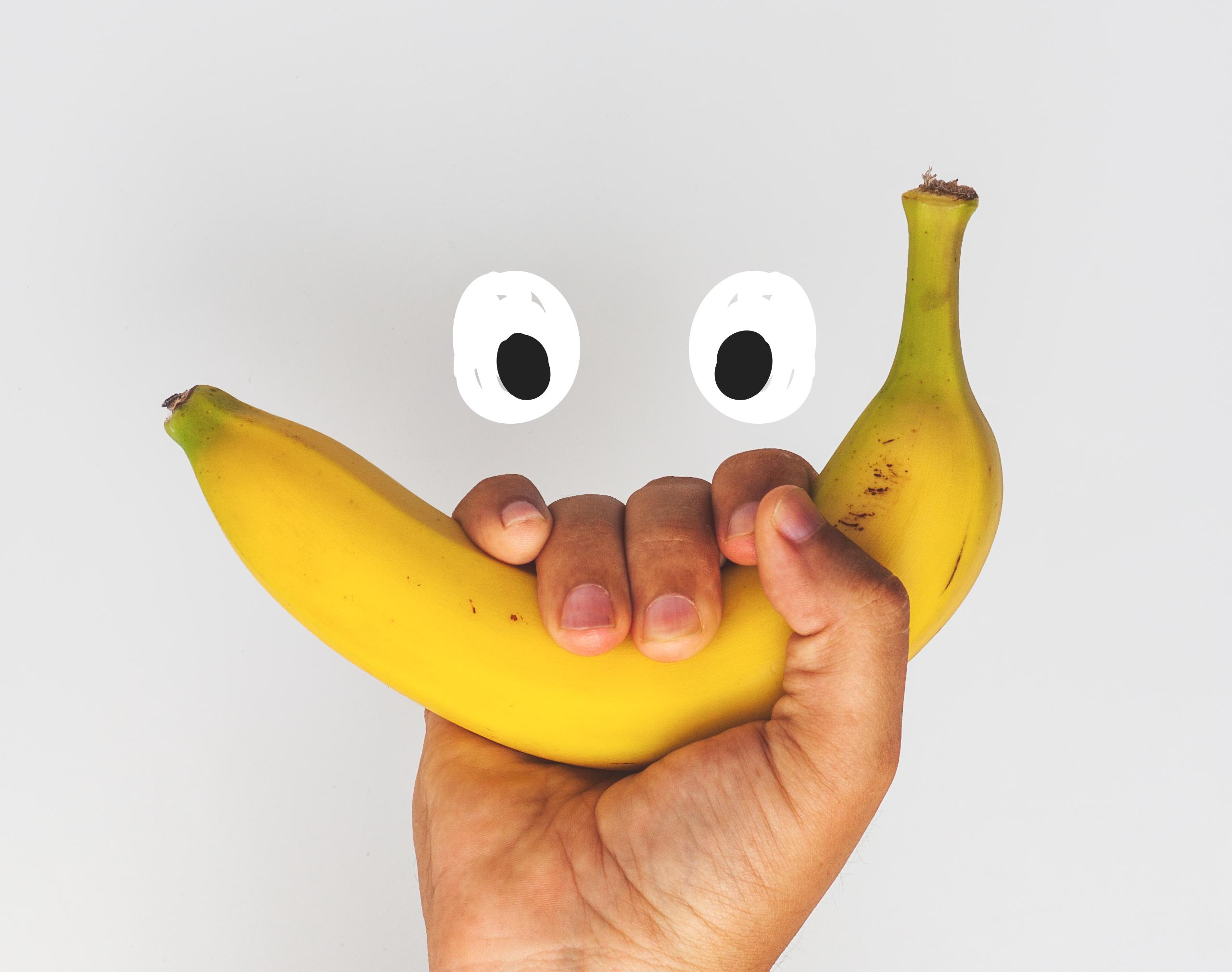 Hand holding a banana making a face